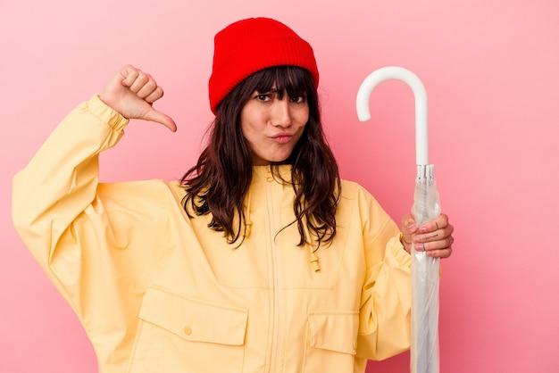 Jonge blanke vrouw met een paraplu geïsoleerd op roze achtergrond voelt zich trots en zelfverzekerd, voorbeeld om te volgen.