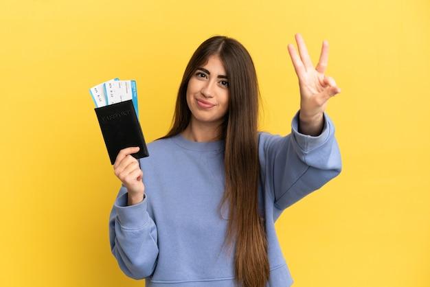 Jonge blanke vrouw met een paspoort geïsoleerd op een gele achtergrond gelukkig en drie tellen met vingers