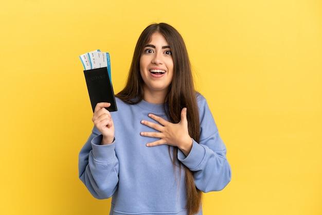 Jonge blanke vrouw met een paspoort geïsoleerd op een gele achtergrond verrast en geschokt terwijl ze naar rechts kijkt