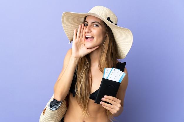 Jonge blanke vrouw met een paspoort voor vakantie geïsoleerd op een paarse achtergrond schreeuwend met wijd open mond