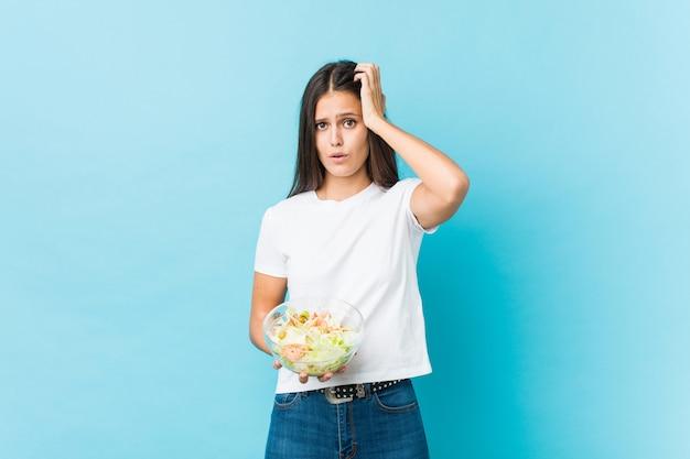 Jonge blanke vrouw met een salade wordt geschokt, heeft ze belangrijke vergadering onthouden.