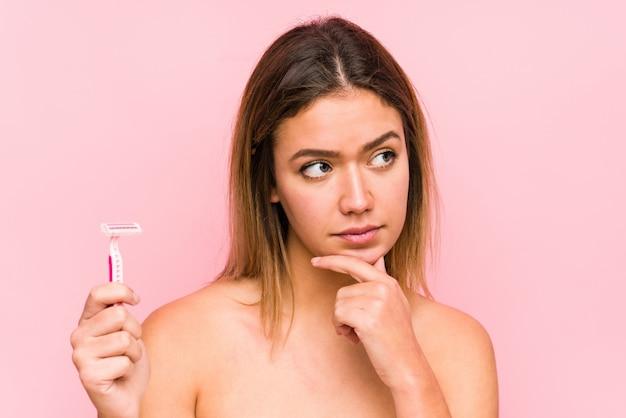 Jonge blanke vrouw met een scheermesje geïsoleerd jonge blanke vrouw met een haarborstel geïsoleerd zijwaarts kijkend met twijfelachtige en sceptische uitdrukking. <mixto>