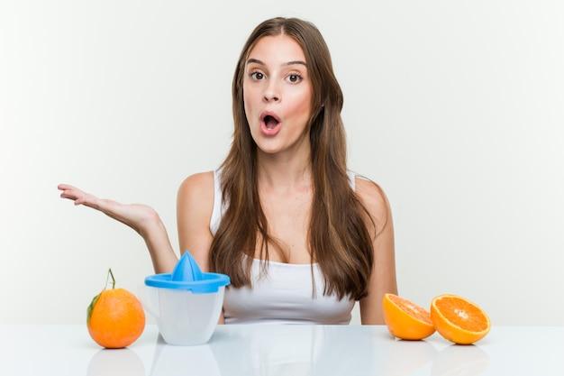 Jonge blanke vrouw met een sinaasappelpers onder de indruk bedrijf kopie op palm.
