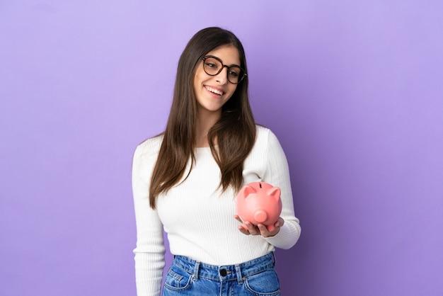 Jonge blanke vrouw met een spaarpot geïsoleerd op een paarse achtergrond, opzij kijkend en glimlachend