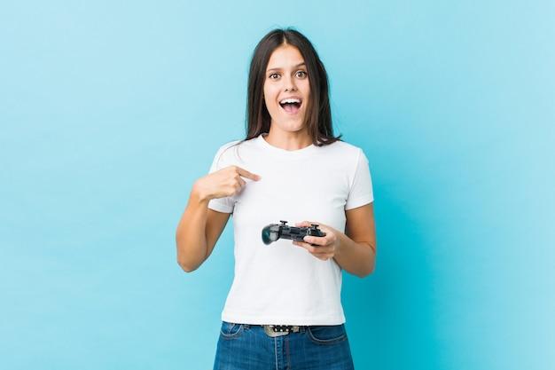Jonge blanke vrouw met een spelbesturing verrast wijzend op zichzelf, breed glimlachend.