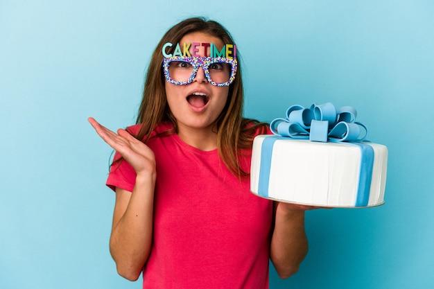 Jonge blanke vrouw met een taart geïsoleerd op blauwe achtergrond verrast en geschokt.