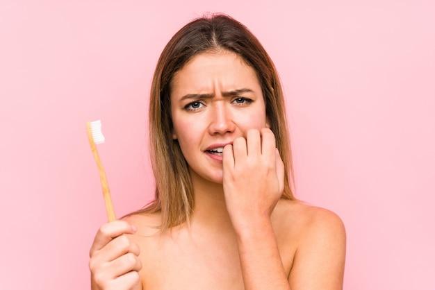 Jonge blanke vrouw met een tandenborstel geïsoleerd vingernagels bijten, nerveus en erg angstig.