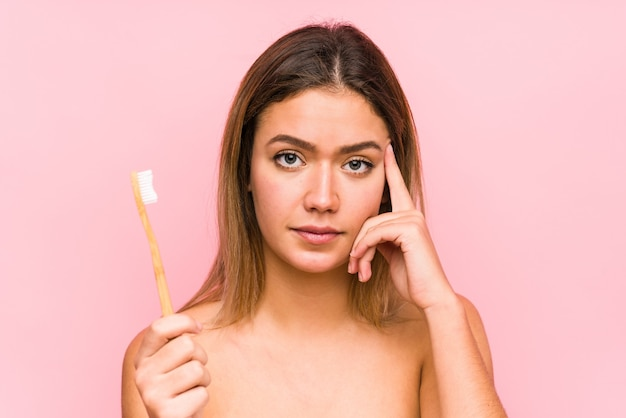 Jonge blanke vrouw met een tandenborstel geïsoleerd wijzend zijn tempel met vinger, denken, gericht op een taak.