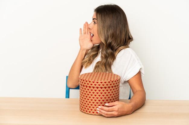 Jonge blanke vrouw met een valentijnsdag doos geïsoleerd schreeuwen en palm in de buurt van geopende mond te houden.