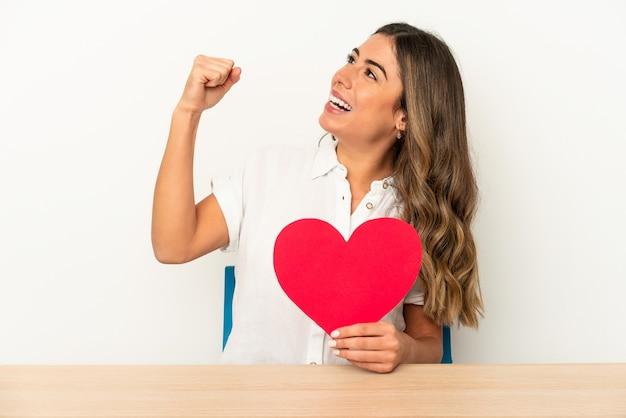 Jonge blanke vrouw met een valentijnsdag hart geïsoleerd verhogen vuist na een overwinning, winnaar concept.