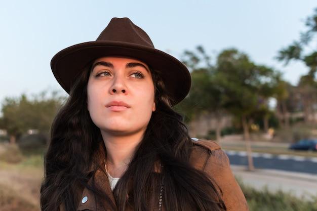 Jonge blanke vrouw met een veedrijfsteruitrusting bij een natuurpark en op zoek in de verte