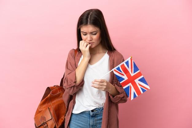 Jonge blanke vrouw met een vlag van het verenigd koninkrijk geïsoleerd met twijfels