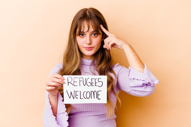 Jonge blanke vrouw met een vluchtelingen welkom bordje wijzende tempel met vinger, denken, gericht op een taak.