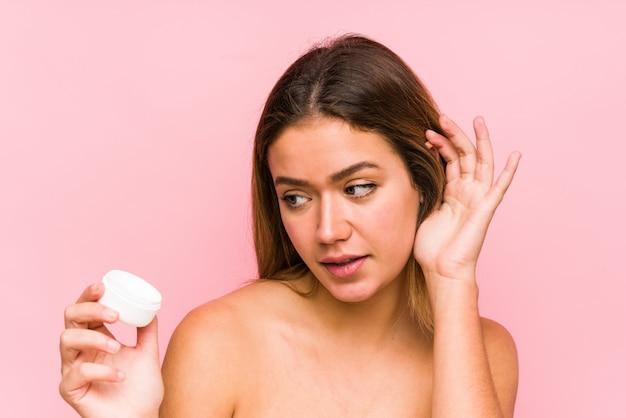 Jonge blanke vrouw met een vochtinbrengende crème geïsoleerd proberen te luisteren van een roddel.