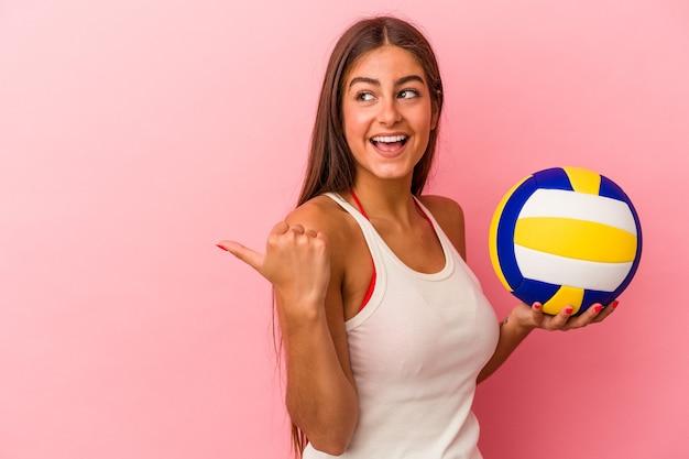 Jonge blanke vrouw met een volleybalbal geïsoleerd op roze achtergrond wijst met duimvinger weg, lachend en zorgeloos.