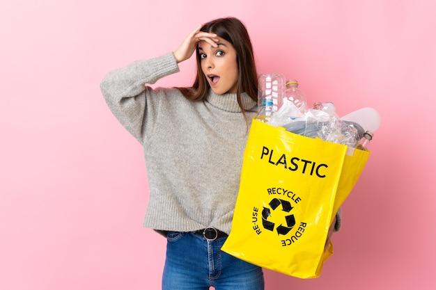 Jonge blanke vrouw met een zak vol plastic flessen om te recyclen geïsoleerd op roze achtergrond doet verrassingsgebaar terwijl ze naar de zijkant kijkt