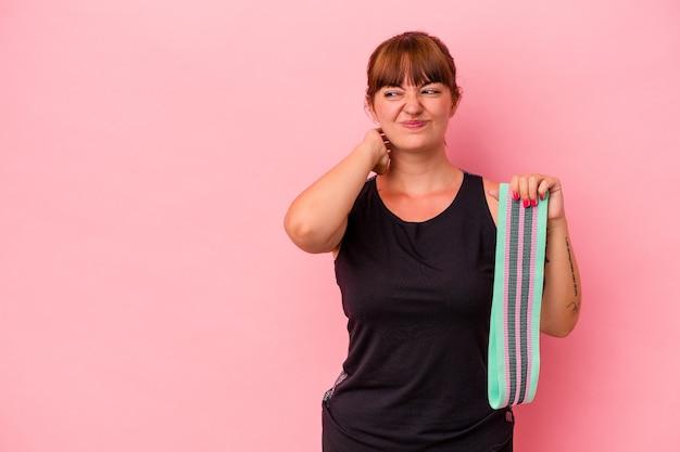 Jonge blanke vrouw met elastische banden geïsoleerd op een roze achtergrond die de achterkant van het hoofd aanraakt, denkt en een keuze maakt.