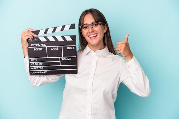 Jonge blanke vrouw met filmklapper geïsoleerd op blauwe achtergrond glimlachend en duim omhoog
