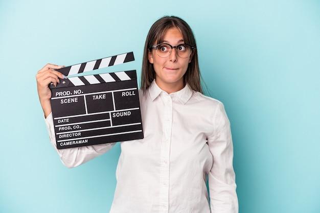 Jonge blanke vrouw met filmklapper geïsoleerd op blauwe achtergrond verward, voelt zich twijfelachtig en onzeker.