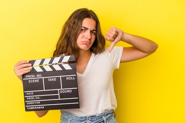 Jonge blanke vrouw met filmklapper geïsoleerd op gele achtergrond met een afkeer gebaar, duim omlaag. onenigheid begrip.