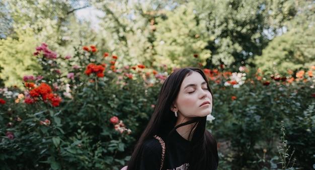 Jonge blanke vrouw met gesloten ogen genieten van lenteweer op tuin met bloeiende rozen.