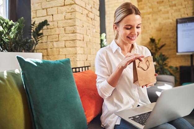 Jonge blanke vrouw met grijze laptop op benen met cadeau in handen