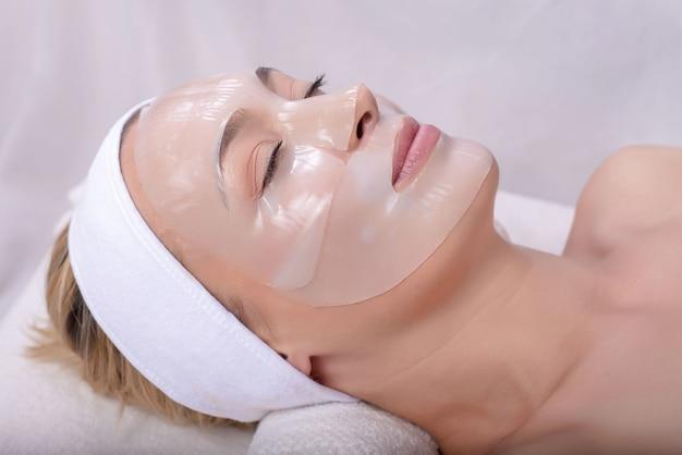 Jonge blanke vrouw met huidmasker op haar gezicht in de spa