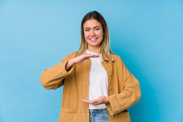 Jonge blanke vrouw met iets met beide handen, productpresentatie.