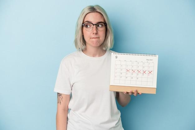 Jonge blanke vrouw met kalender geïsoleerd op blauwe achtergrond verward, voelt zich twijfelachtig en onzeker.