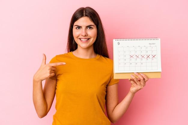 Jonge blanke vrouw met kalender geïsoleerd op roze achtergrond persoon die met de hand wijst naar een shirt kopieerruimte, trots en zelfverzekerd