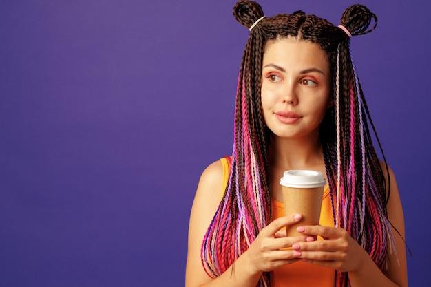 Jonge blanke vrouw met kleurrijke lange cornrows met een kopje koffie tegen paars