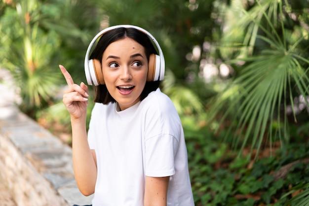 Jonge blanke vrouw met koptelefoon buitenshuis van plan om de oplossing te realiseren terwijl het opheffen van een vinger