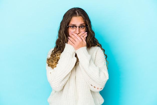 Jonge blanke vrouw met krullend haar die mond bedekt met handen op zoek bezorgd.