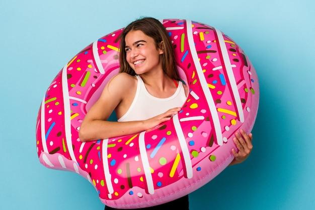 Jonge blanke vrouw met opblaasbare donut geïsoleerd op blauwe achtergrond kijkt opzij glimlachend, vrolijk en aangenaam.