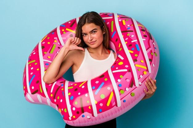 Jonge blanke vrouw met opblaasbare donut geïsoleerd op blauwe achtergrond met een afkeer gebaar, duim omlaag. onenigheid begrip.