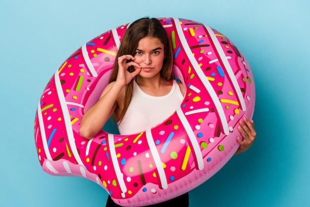 Jonge blanke vrouw met opblaasbare donut geïsoleerd op blauwe achtergrond met vingers op lippen die een geheim houden.