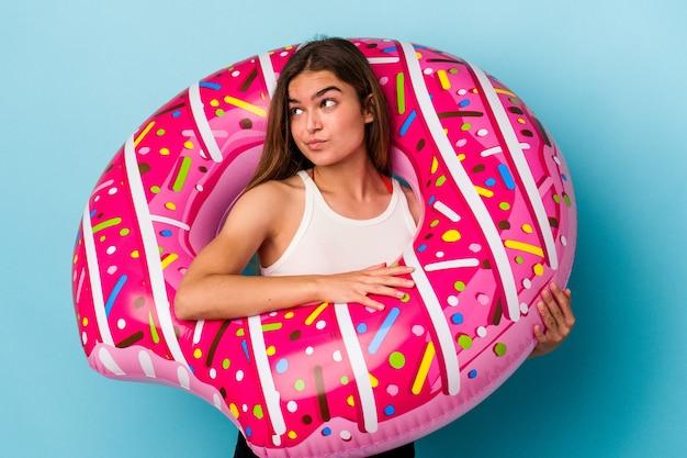 Jonge blanke vrouw met opblaasbare donut geïsoleerd op blauwe achtergrond verward, voelt zich twijfelachtig en onzeker.