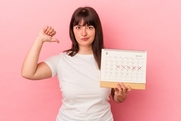 Jonge blanke vrouw met overgewicht met kalender geïsoleerd op roze achtergrond voelt zich trots en zelfverzekerd, voorbeeld om te volgen.
