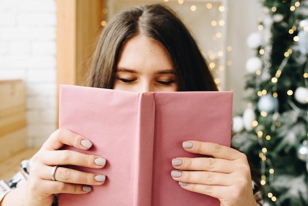 Jonge blanke vrouw met paars boek in de buurt van versierde kerstboom