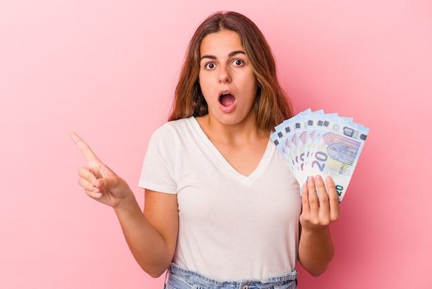 Jonge blanke vrouw met rekeningen geïsoleerd op een roze achtergrond die naar de zijkant wijst