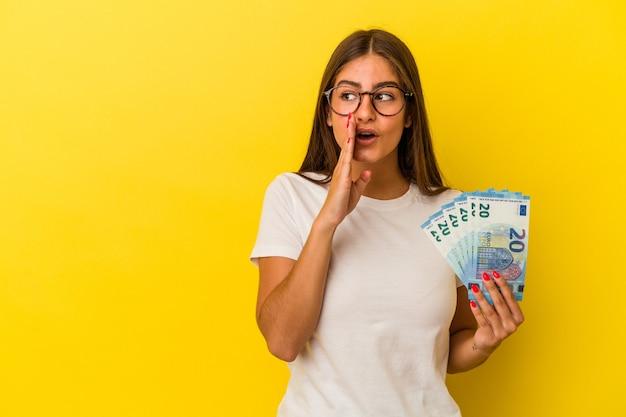 Jonge blanke vrouw met rekeningen geïsoleerd op gele achtergrond zegt een geheim heet remnieuws en kijkt opzij