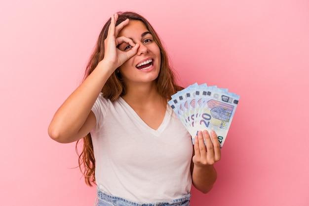 Jonge blanke vrouw met rekeningen geïsoleerd op roze achtergrond opgewonden houden ok gebaar in de gaten.