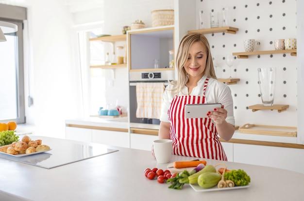 Jonge blanke vrouw met rood gestreepte schort met mok en kijkt naar recept op telefoon in de keuken
