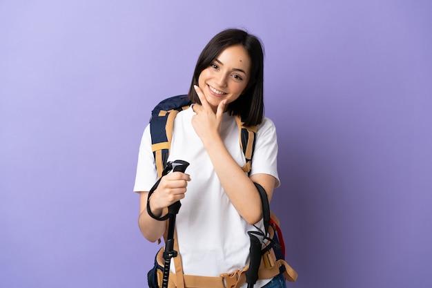 Jonge blanke vrouw met rugzak en wandelstokken geïsoleerd op blauw blij en lachend