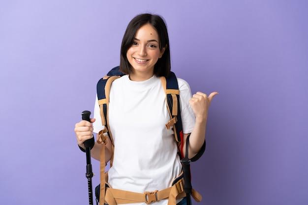 Jonge blanke vrouw met rugzak en wandelstokken geïsoleerd op blauw wijzend naar de zijkant om een product te presenteren