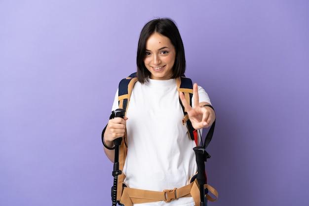 Jonge blanke vrouw met rugzak en wandelstokken geïsoleerd op blauwe achtergrond glimlachend en overwinningsteken tonen