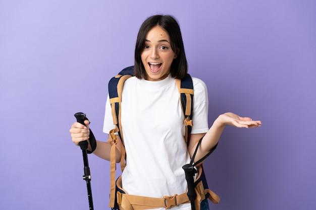 Jonge blanke vrouw met rugzak en wandelstokken geïsoleerd op blauwe achtergrond met geschokt gelaatsuitdrukking