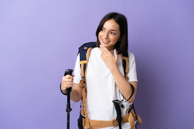 Jonge blanke vrouw met rugzak en wandelstokken geïsoleerd op blauwe achtergrond opzoeken tijdens het glimlachen