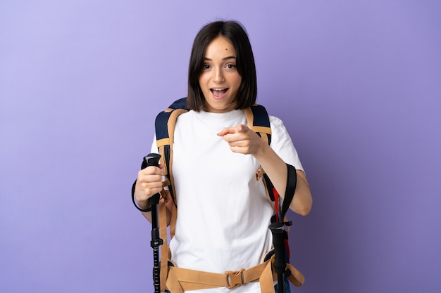 Jonge blanke vrouw met rugzak en wandelstokken geïsoleerd op blauwe achtergrond verrast en wijzend naar voren