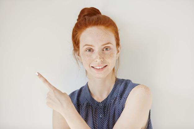 Jonge blanke vrouw met schone sproeten huid en gember haar wijzend haar vinger zijwaarts, iets te demonstreren op witte blinde muur